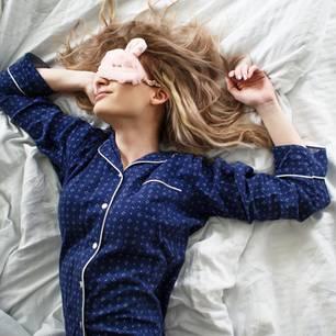 Warum du nicht auf der rechten Seite schlafen solltest: Frau mit Pyjama und Schlafmaske liegt im Bett