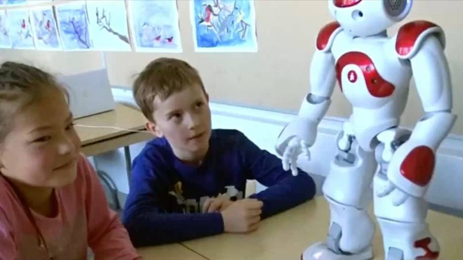 Roboter in der Grundschule: Schüler guckt aufmerksam zu Roboter