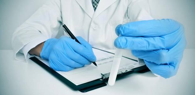 USA: Ein Arzt füllt ein Formular aus und hat ein Reagenzglas in der Hand