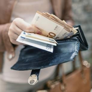 Reich werden: Frau mit Portemonnaie voller Geld