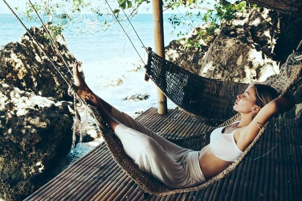 Reich werden: Frau liegt am Meer in Hängematte