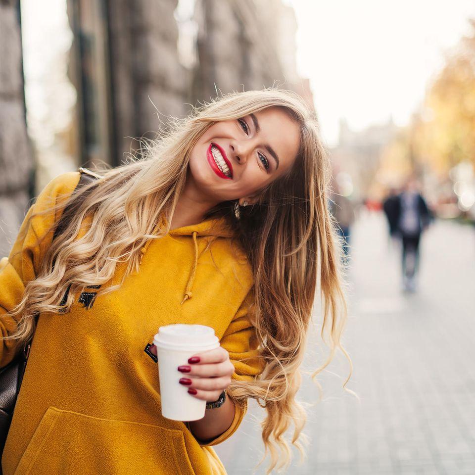 Pille und Kaffee: Strahlende Frau mit Coffee To Go in der Hand