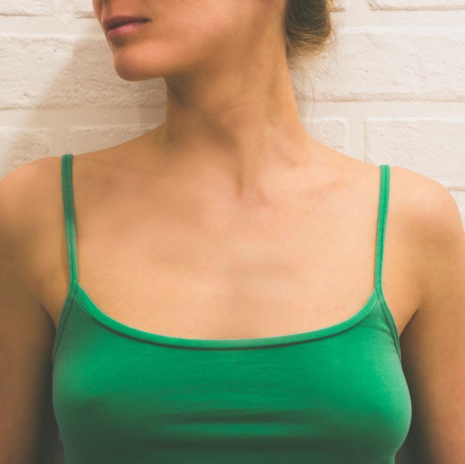 Eine junge Frau mit Spaghetti-Top, durch das man die Brustwarzen sieht