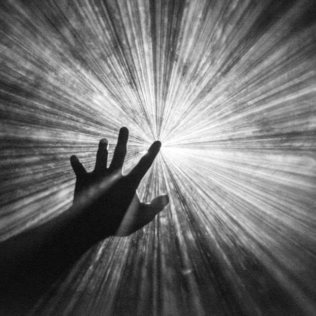 Leben nach dem Tod: Hand streckt sich nach einem Licht aus