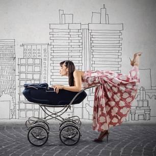 Modische Mama auf Highheels beugt sich knutschend über den Kinderwagen