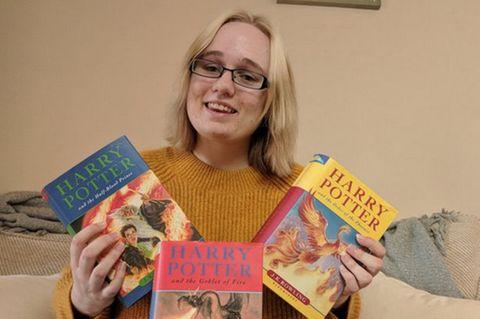Reich mit Harry Potter: Frau hält die kostbaren Bücher hoch
