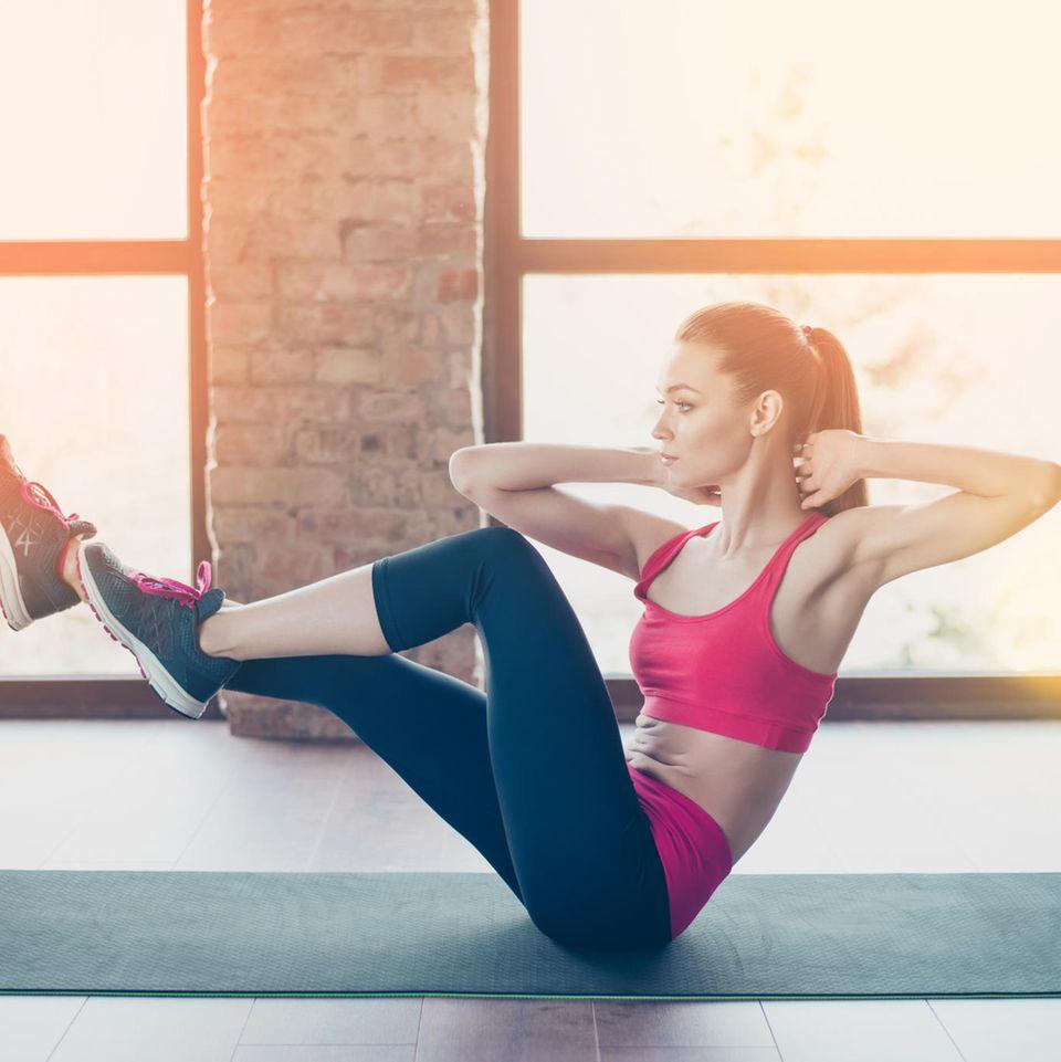 Übungen zum Abnehmen: Frau macht Bauchübung