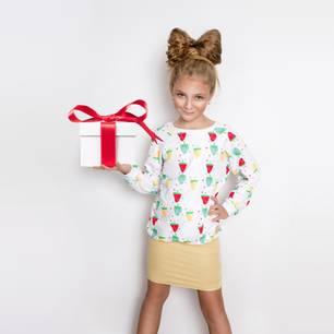 Kind hält Geschenk hoch und schaut selbstbewußt