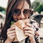 Immer nur Salat essen: Frau beißt in Burger