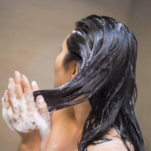 Shampoo ohne Sulfate: Frau beim Haarewaschen unter der Dusche