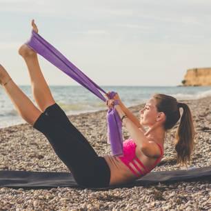 Theraband Übungen: Frau trainiert mit Theraband am Strand