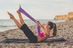 Theraband Training: Frau trainiert mit Theraband am Strand