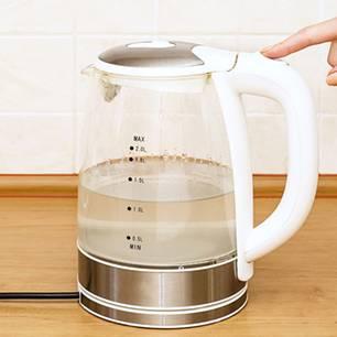 Wasserkocher, Hand drückt auf den Einschalteknopf