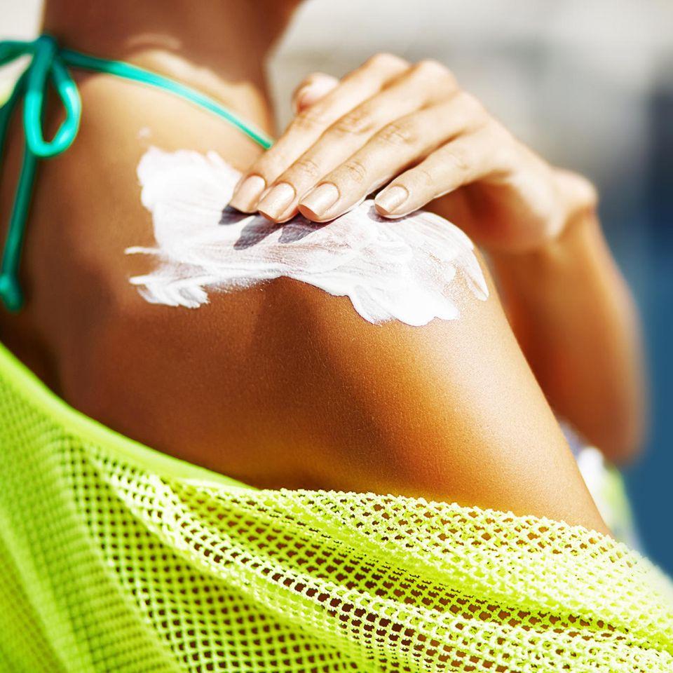 Mineralische Sonnencreme: Frau cremt sich die Schulter ein