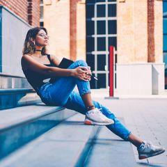 Eine ausgeglichene Frau sitzt auf einer Treppe in der Sonne