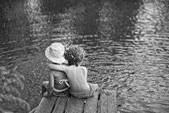 Zwei Kinder sitzen Arm in Arm an einem See