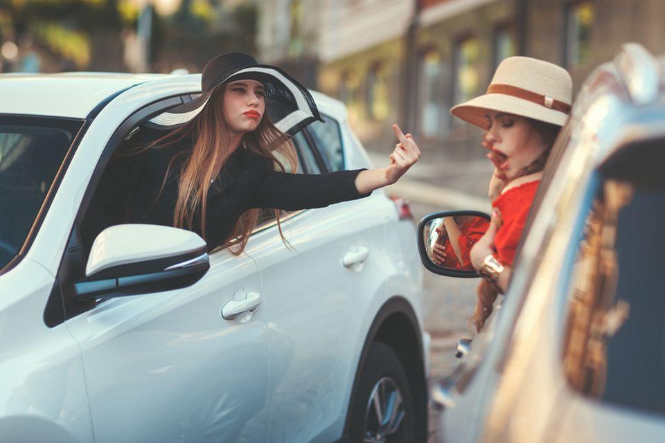 Sternzeichen mit schwierigem Charakter: Frau macht obszöne Geste im Straßenverkehr