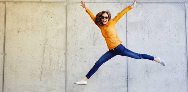 Glückliche Sternzeichen: Frau springt jubelnd in die Luft