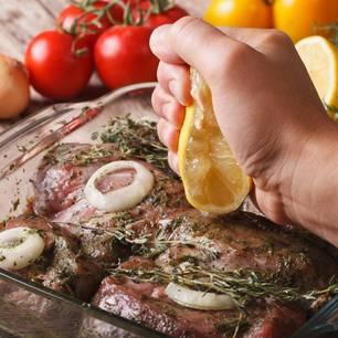 Fleisch marinieren: Hand verteilt Zitrone über Grillfleisch
