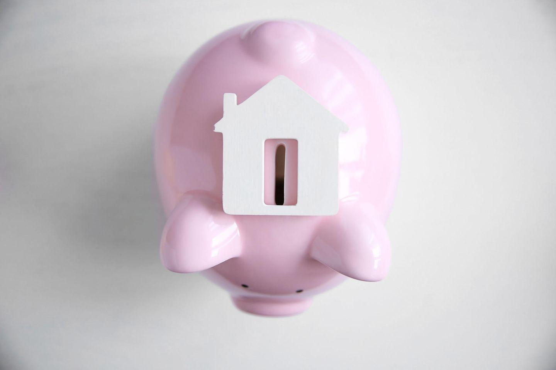 Immobilie als Altersvorsorge: Rosa Sparschwein mit Haus darauf
