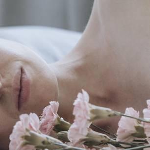 Unerfüllte Sehnsucht: Frau liegt seitlich und schaut nachdenklich