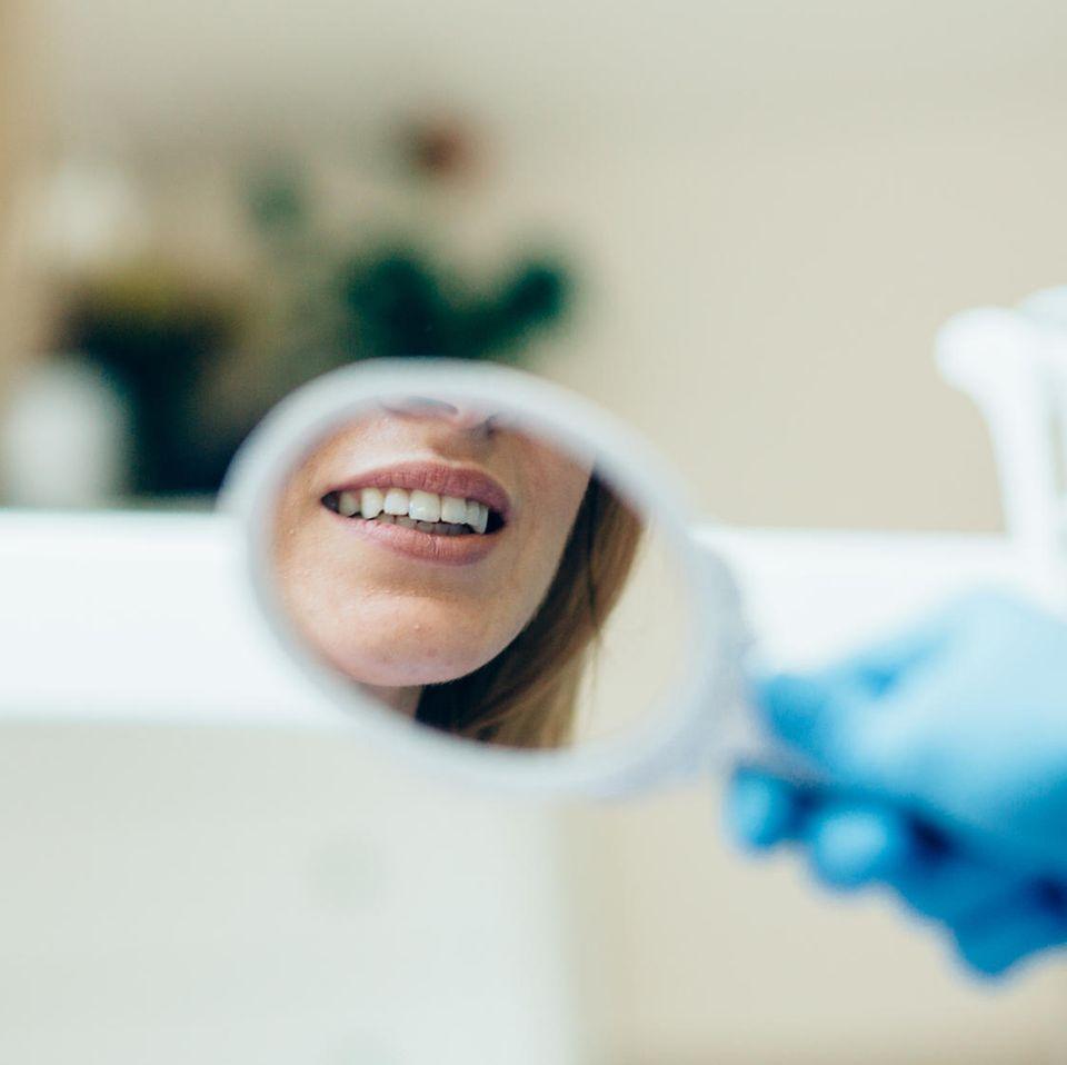 Zahnprobleme Wechseljahre: Frau betrachtet Zähne im Spiegel