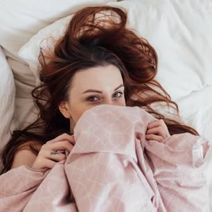 Tipps gegen Mundgeruch: Frau versteckt Mund unter Decke