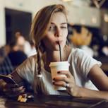 iPhone-Tricks: Frau zwinkert über ihr iPhone in die Kamera