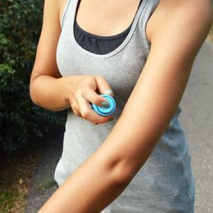 Was hilft gegen Mücken? Frau mit Mückenspray
