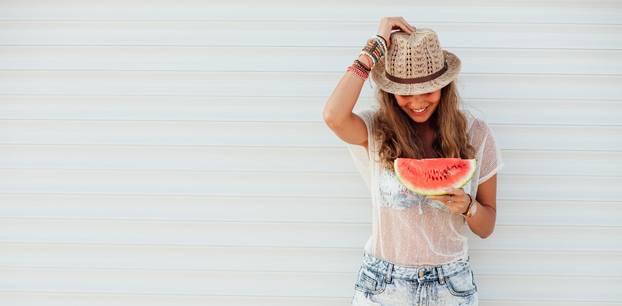 Frau isst eine Melone