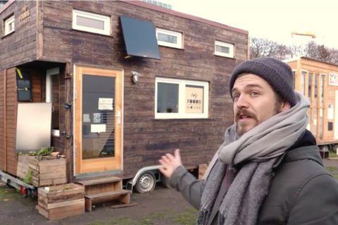 Tiny House für Obdachlose: Mann zeigt auf Haus