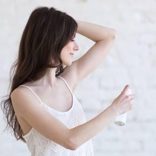 Aluminiumfreie Deos: Frau sprüht Deo unter die Achseln