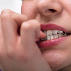Nägel kauen: Frau beißt auf ihre Fingernägel