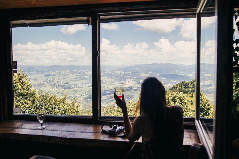 Außergewöhnliche Hotels in Europa: Frau sitzt am Fenster und schaut auf eine Landschaft