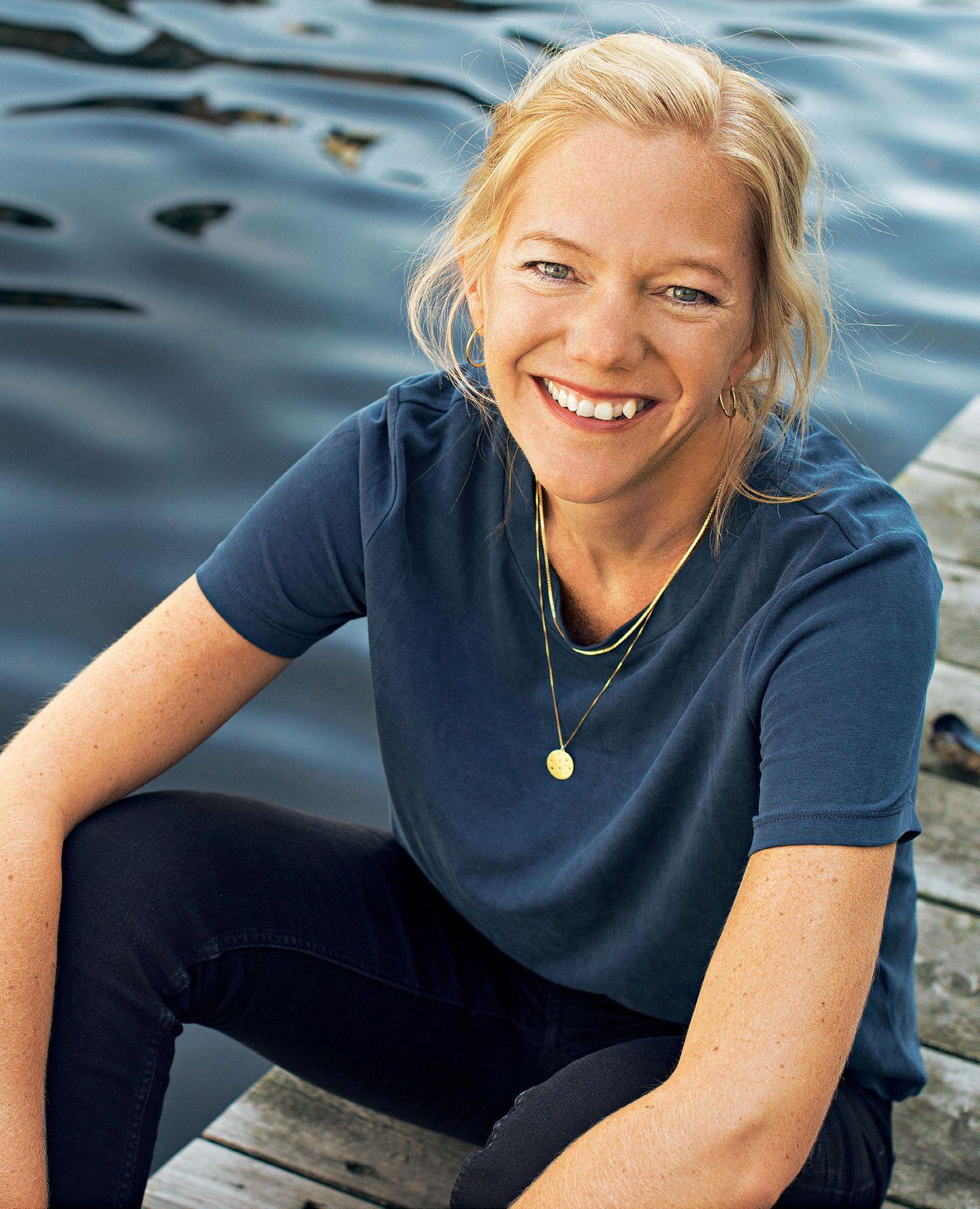 Maja Lunde: Die Autorin sitzt auf einem Steeg am Wasser
