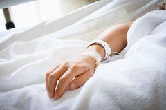 Kinderhand in einem Krankenhausbett