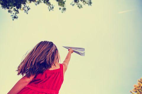 Ein Mädchen spielt mit einem Papierflieger