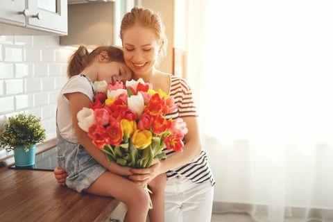 Warum feiern wir Muttertag? Tochter überreicht Blumenstrauß an Mama