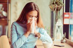Nasenbluten: Frau im Café mit Taschentuch vor der Nase