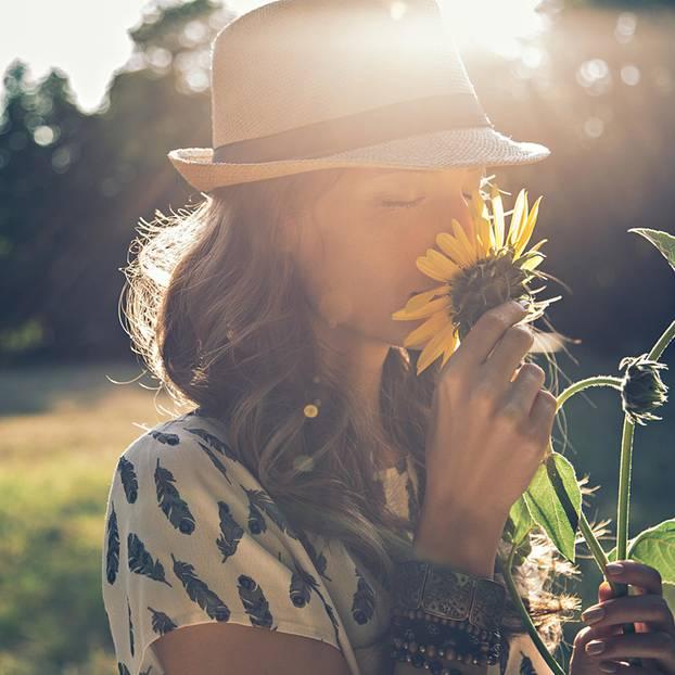Duft-Unverträglichkeit: Frau riecht an einer Sonnenblume