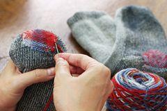 Socken stopfen: Frau stopft Socken