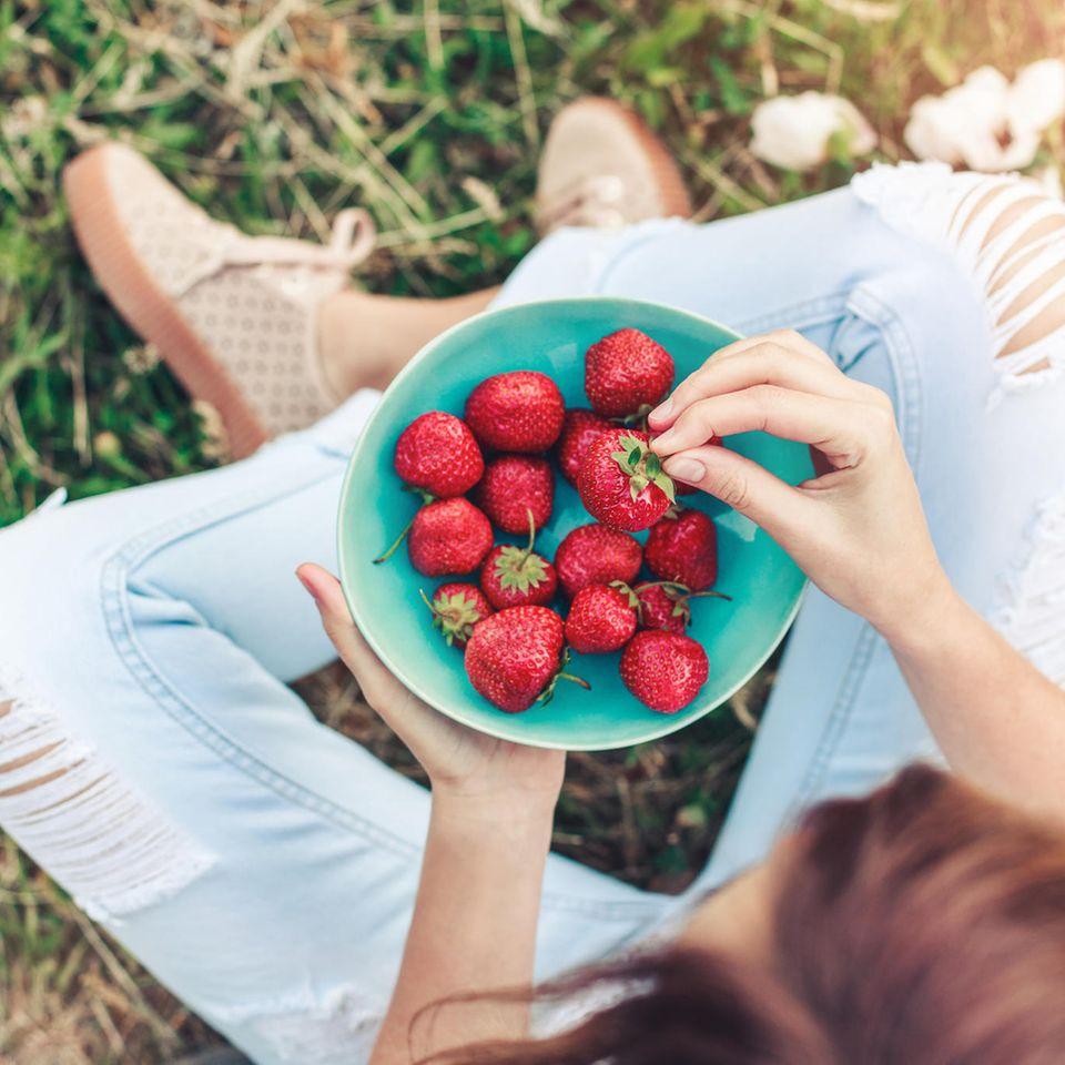 Kann Essen wirklich heilen: Frau isst Erdbeeren auf einer Wiese