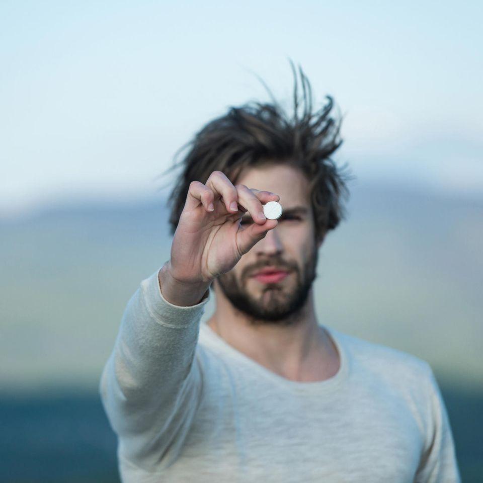Pille für den Mann: Mann hält Pille in die Kamera