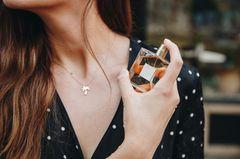 Frau hält Parfumflakon in der Hand