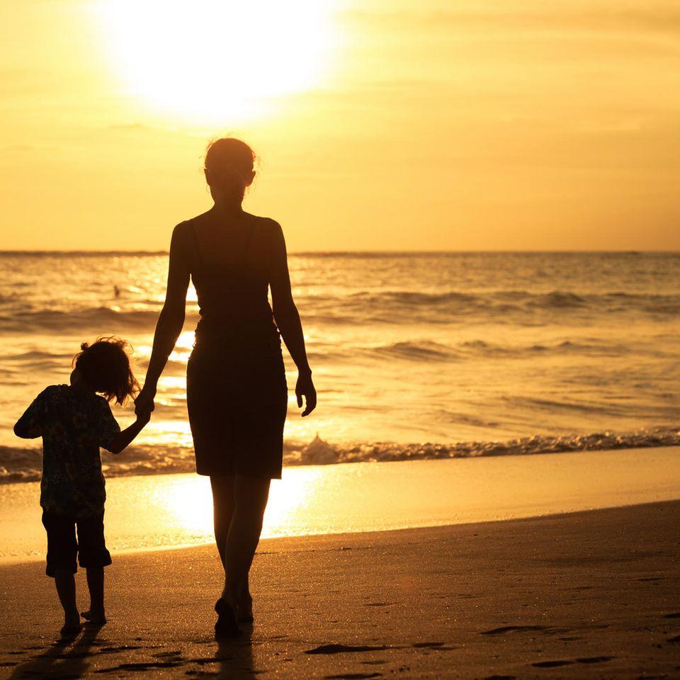 Unsichtbare Mutter: Mutter mit Kind am Strand