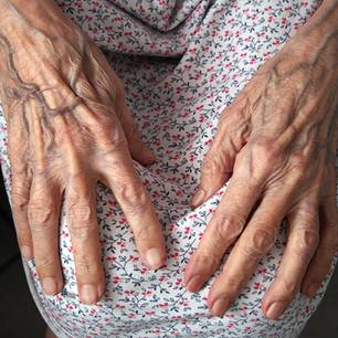 Die Hände einer alten Frau in ihren Schoß gelegt