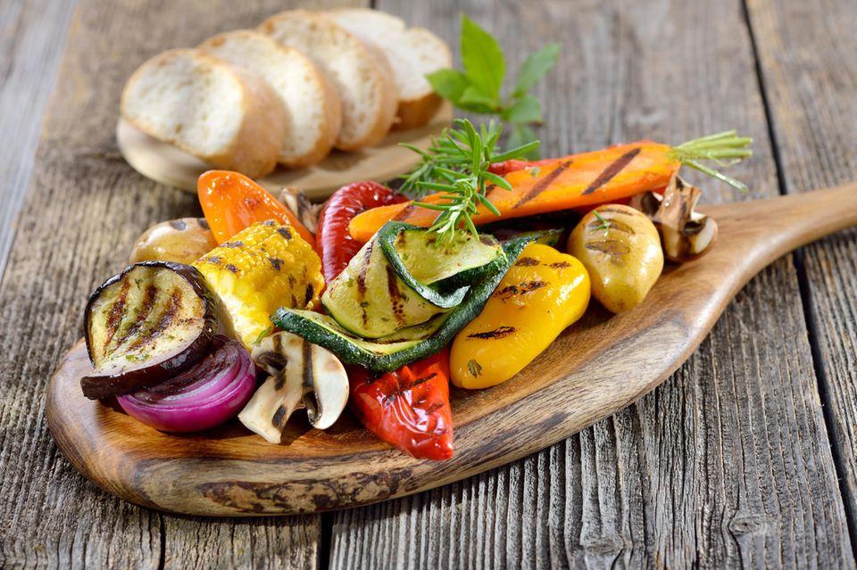 Vegan grillen: Gegrilltes Gemüse auf einem Schneidebrett