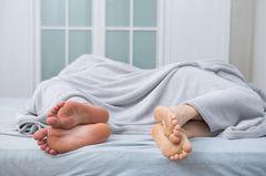 Ein Paar im Bett mit einander zugewendeten Rücken