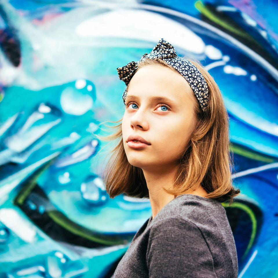 Pubertät: Jugendliches Mädchen vor einer bunten Wand