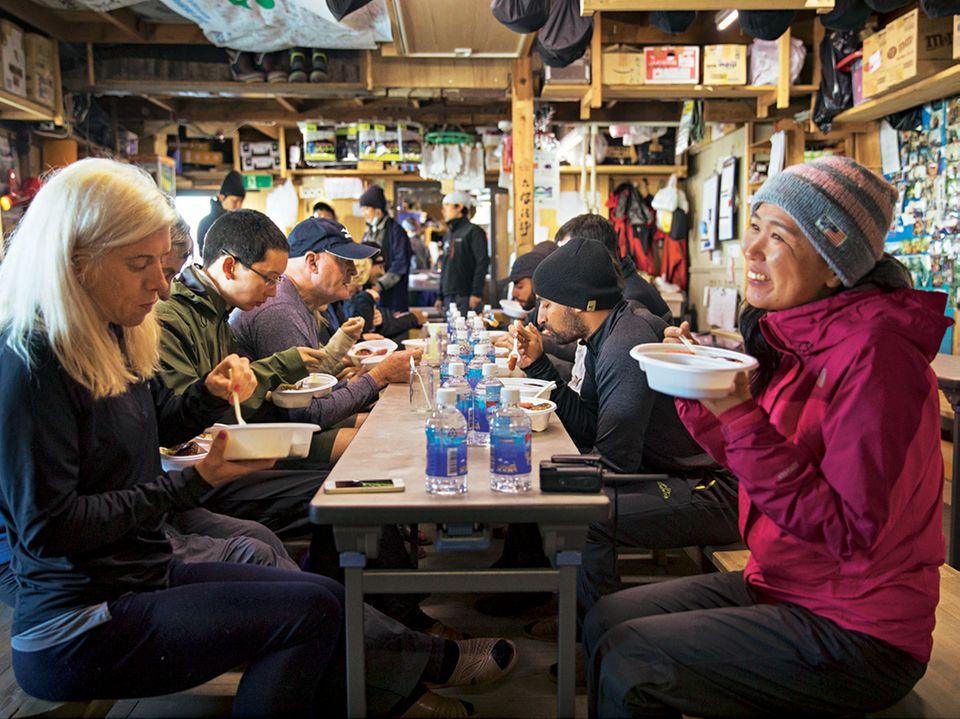 Japan: Die Wander-Gruppe beim essen in der letzten Hütte vor dem Gipfel